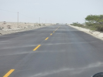 Lines of sand blowing across the road show the strong winds